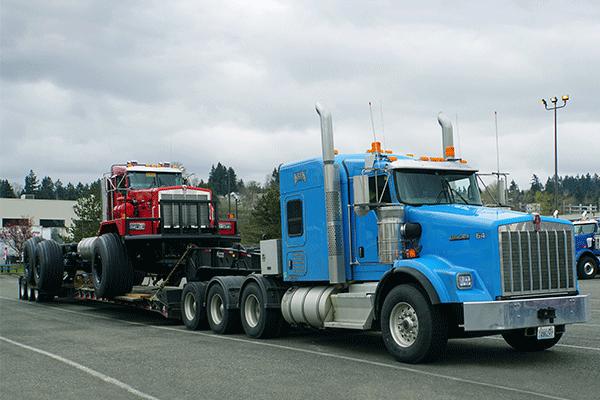 Open deck trailer hauling equipment