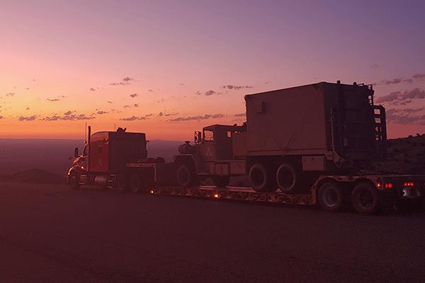 low boy trailer hauling construction equipment