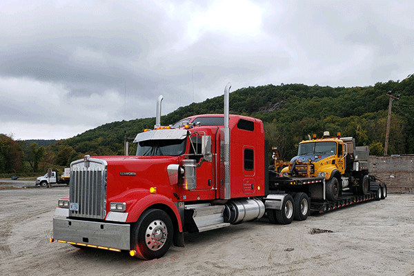 low boy trailer hauling machinery