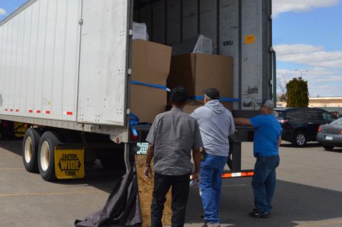 Three men unloading a dry van trailer