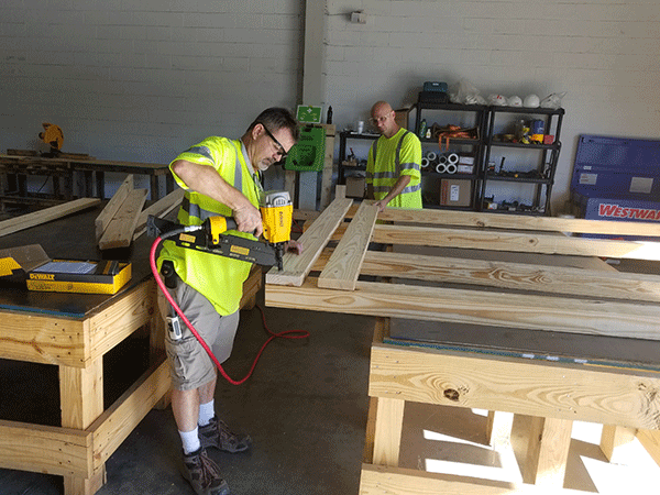 Two men building a crate for packing solutions