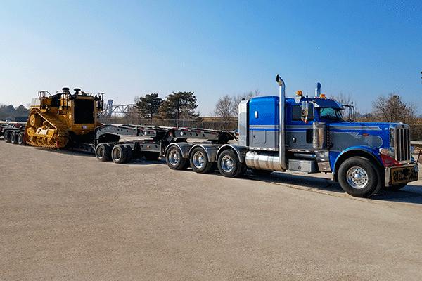 Open deck trailer hauling heavy machinery