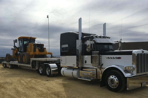Drop deck trailer loaded with construction equipment