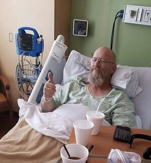 Dawain gives thumbs up while recovering in his hospital bed