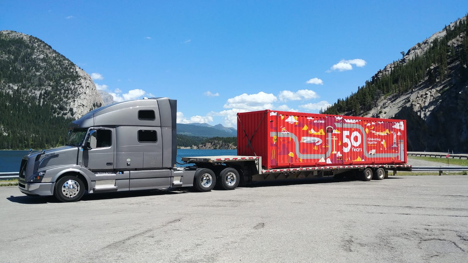 ATS truck parked in front of mountain lake with PERI container on trailer
