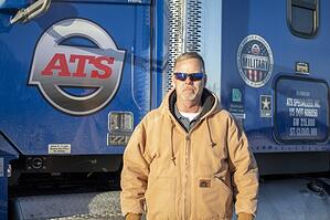 ATS Driver, Mike, standing in front of his truck