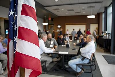 Veterans share story over breakfast with American flag in foreground